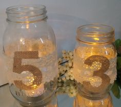Table number canning jar-wedding receptions-trimmed in ivory lace, satin ribbon, & brown burlap numbers. Rustic country style guest favor. by TheAtticShelf on Etsy