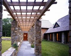 Beautiful combination of the wood trellis and stone pillars to enclose this walkway as well as provide outdoor seating options.