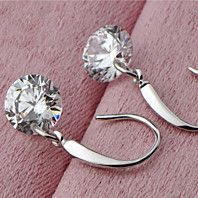 """These stunning sterling silver drop earrings hold a Naked 2.0 carat round Swarovski Element crystal.They're perfect for everyday wear and add a touch of elegance to any outfit. They also make a beautiful gift for any occasion. Product Details:2.0 Carat Round Swarosvki Element CrystalsCrystal size is 8mm925 stamped sterling silverAnti-tarnish finishAbout 1"""" Drop"""