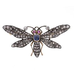 A butterfly brooch, the rose cut diamonds set to the abdomen and wings of a butterfly, with a sapphire and rubies set to the body and head. Measuring 46mm by 22mm.