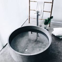 Minimalist style grey concrete bathroom / round bath /tub