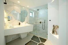 ασύμμετρα σχήματα σε χρώματα του νερού και του φωτός και της γης δένουν αρμονικά στο μπάνιο του ξενοδοχείου Santorini Grace