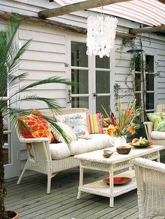 This simple white wicker set is dressed up with accessories such as cushions, pillows, and throws. To add much-needed shade, the fabric awning was added. (Photo: IPC Images)