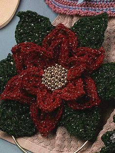 """Poinsettia Towel Topper - Add a festive touch to your kitchen this holiday season with a crochet Poinsettia Towel Topper stitched using metallic gold twist yarn, gold beads and a 4"""" gold metal ring. Finished size is 9"""" x 9"""" not including gold ring. Skill Level: Easy  Designed by Patricia Hall  free pdf from FreePatterns.com"""