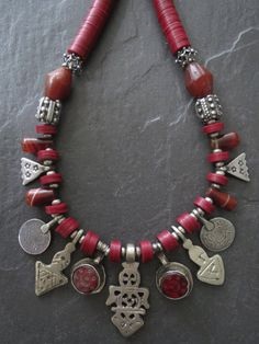 An alluring tribal ethnic necklace of fabulous beads and amulets make this a show stopping piece. The rich warm maroon color throughout always reminds me of the robes of Tibetan monks. For some reason it was really difficult to capture the true color in this piece and the lens tended to portray dark pink rather than the true deep rich dark maroon.  The beads include four ancient Carnelian bi-cone beads excavated in Mali from the 1600s, 4 Czech Bohemian top-drilled glass trade beads and…