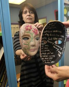 Maria Scaros-Mercado shows a mask made by a woman in her domestic violence support group. The reflection at left represents what the victim shows the world, while the inside of the mask, right, represents what the victim is really going through. Photographed at the Women's Center of Greater Danbury on Thursday, May 3, 2012. Scaros-Mercado is a drama therapist and licensed creative arts therapist. Photo: Jason Rearick / The News-Times