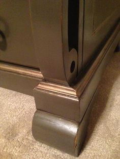 Detail view of leg on upcycled TV console.  Stained top and chocolate painted base with gold wax accents.