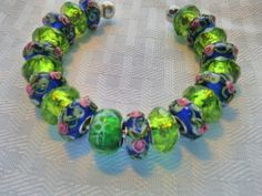 Pink rosebuds adorn this green and blue beaded bangle.