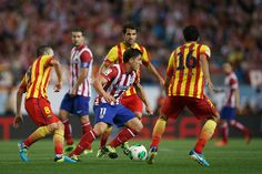 Cristian Rodriguez (2ndL) of Atletico de Madrid competes for the ball with Andres Iniesta (L) of FC Barcelona and his teammate Sergio Busquets (R) during the Spanish Super Cup first leg match between Club Atletico de Madrid and FC Barcelona at Vicente Calderon Stadium on August 21, 2013 in Madrid, Spain.