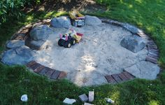 Sandbox for a kid who is all about construction! Rocks and brick!