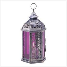 Royal purple shows its romantic side as it banishes the darkness with its gorgeous amethyst glow. Rich stained glass panels are elegantly offset by ornate cutwork and an antique pewter finish. Weight 1.3-pound. Iron and glass. Candle not included. 5 3/4-inch by 5 3/4-inch by 11-1/2-inch high.