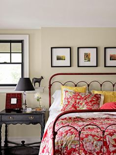 An iron bed from Sundance, plus a Pottery Barn quilt, offers a hit of color in this guest room.