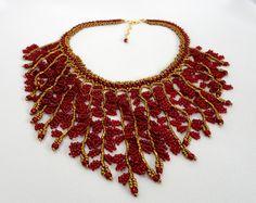 Maxi colar confeccionado com miçangas vermelhas e dourado queimado. Com acabamentos em metal dourado. <br>Comprimento :41 cm + 5 cm de corrente extensora. <br>Largura meio do colar: 11 cm