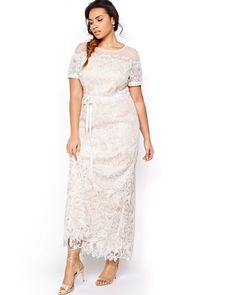 AVAILABLE ONLINE ONLY. Express yourself beautifully on your wedding day with a plus size wedding dress just like you: fun, sexy, trendy, gorgeous. This dress does what it wants with its rich beige coloring covered in bright white contrasting lace. The lace gives way to delicate sheer mesh for an off-shoulder look. Flattering maxi cut, perfect for shaped, curvy, and slim silhouettes, off-shoulder look, sash at waist, short sleeves, fully lined and covered in lace, 54 inch length, Violets…