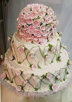 Beautiful cake with lattice work and lots of tiny pink roses.  Love the round layer on the top covered with the roses.  ᘡղbᘠ