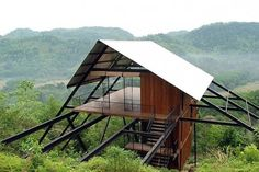 """Bungalow Mathugama is a gorgeous forest dwelling designed by architect Narein Perera that """"touches the earth lightly."""" Standing tall on stilts in the Sri Lankan jungle, the breezy structure has minimal impact on the ground below. The residence is made from steel, timber and locally sourced bamboo, and its shape pays homage to traditional Chena watch-huts."""