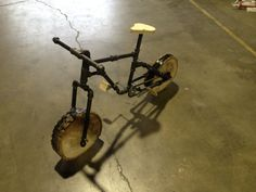 Steel pipe mountain bike with solid wooden wheels and working crank.
