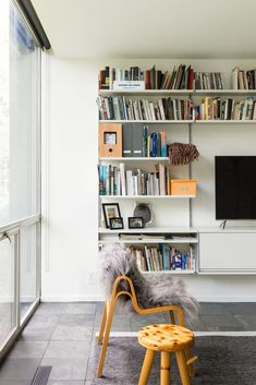 A Wilhelmina chair by Ilmari Tapiovaara furnishes the living area. Tagged: Living Room, Slate Floor, Shelves, Chair, Storage, Rug Floor, and Stools.  Photo 7 of 12 in A New York Transplant Remakes One of Mies van der Rohe's Coveted Townhouses in Detroit