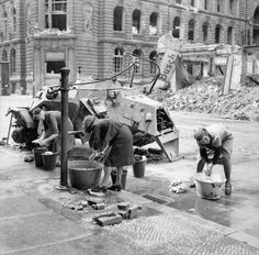 WW2 ¥ (1945) German women doing their washing at a cold water hydrant in a Berlin street. A knocked-out German scout car stands beside them, 3 July 1945.