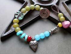 Pulseira artesanal de LORELEI EURTO (2009) -Colorful beaded bracelet with brown waxed linen cording, a Pewter heart focal from Green Girl Studios, ceramic coin bead from Jubilee, glass, ruby quartz, fuschia briolette, amazonite, and Bali glass rounds. Silver button.