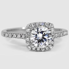 This classic halo engagement ring features French pavé diamonds on the band and embraces the center gem in a brilliant halo.
