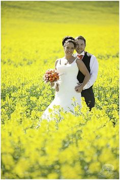 www.LinusMoranPhotography.co.uk Wedding Couple standing in a field of rapeseed -  Stockbridge Farm Wedding, Dorset