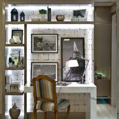Para destacar os nichos foi utilizada uma iluminação de destaque. Além disso a iluminação ajudou a enfatizar a textura da parede. Por ter uma boa iluminação, o local ainda pode ser utilizado como local de trabalho.