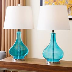 These Abbyson Living Luciana table lamps will be a stylish addition to your home. The transparent turquoise blue glass base is striking below the ivory lamp shade. These lamps will bring balanced harmony to your room.