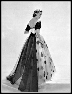 Model in evening gown of white organza with black circles, and black mousseline scarf held by two white flowers trailing in floating train in back by Nina Ricci | Photo Georges Saad, 1951