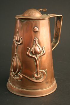An Art Nouveau design copper jug of tapering form with domed and hammered lid, the body with stylized flowers.