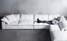 The dreamy 'Cloud' sofa, inspired by British designer, Timothy Oulton (seen here), in white Belgian linen will lull you away to a weekend nap in Malibu or the Hamptons whenever you make the time. Available from Restoration Hardware.