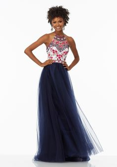 Wear this charming floral embroidered and tulle gown to your prom and feel like a Bohemian princess. This chic gown has a floral design on the high neck halter bodice and a band that defines the waist. The layered tulle skirt is soft and adds life to the silhouette. This dress is available in Navy, Coral, and Scarlet.