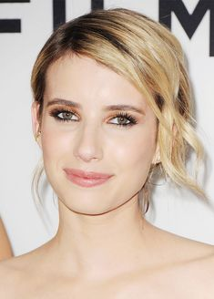 Emma Roberts // gold eye shadow, spidery black lashes, and a texturized side part, pulled back