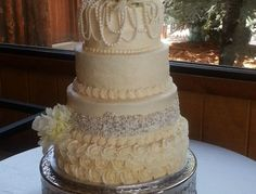 4 tire round wedding cake decorated with sugar pearls, silver dragees, sparkle sugar and rosettes.