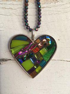 Studio 9 artiste Elizabeth Grindon créé ce pendentif mosaïque de minuscules, à l'unité couper des morceaux de verre teinté, verre dichroïque et miroir coloré. Tons de bleu, turquoise, vert, or et rose. Environ 1,75 pouces de large par 1,75 pouces de haut. Plaque d'argent base et fermoir mousqueton. Se bloque sur un brin de 20 pouces à la main-tendu de petites perles en cristal iridié reflétant les tons de vert, rose et turquoise.