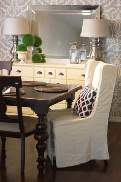 Table.CurvyLegs.Wallpaper.Yellowsideboard.SlipcoveredChairs.Darkwoodfloors.