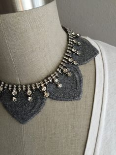 This beautifully crafted collar necklace is made with grey heather melange embroidered collar necklace carefully crafted to fall softly over your shoulders highlighting just the right amount of sparkle in an intricate royal rhinestone necklace embellishment. Collar is embroidered with a soft cottony thread and crystal rhinestones are set into a beautiful antique dark silver metal setting. Collar is approx. 5cm at widest part, back is closed with an adjustable beige flowy gros grain closure…