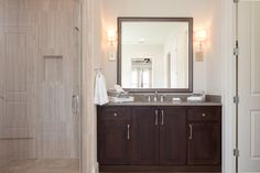 Dark wood solidifies the master vanity, while soft creams add to the tranquility of the space.