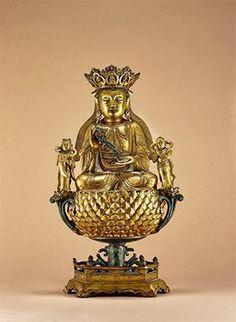 """观音 创作年代 明 尺寸 高42cm 估价 600,000 - 800,000 RMB 成交价 -- 作品分类 佛教文物其它 作品描述 中原,铜鎏金  童男童女是一个成语,就是指未婚的男孩与女孩。出自西汉·司马迁《史记·封禅书》。观音大士的塑像两边,有一对童男童女,男的叫""""善财"""",女的叫""""龙女""""。他们可以为人类带来福泽和财富,是最吉祥的神灵之一。 此尊观音头戴五叶冠,冠上有化佛,延续了唐代风格。观音双眉较长,两眼微微下视,嘴角略有上翘,稍带淡淡的微笑,给人以亲切慈祥的感觉。两耳挂圆珰。胸前饰繁密璎珞,珠纹刻画有力,设计华美。身穿通肩式袍衣,下身着长裙,裙折优美流畅,衣缘刻精美莲花纹。双腿盘曲结跏趺坐于六角式莲池形台座承托的仰莲,层次分明,饱满厚重,莲花座莲瓣圆润丰满,显示其旺盛的生命力。左右两侧各生侧莲花,其上站立童男童女。此尊观音比例适中,线条简洁流畅,丰腴而不虚,近人而不俗。通体鎏金,保存完好,制作工艺上乘,有别于多数泥金、漆金之器,是尊难得一见的汉传佛教造像精品。 参阅:故宫博物院编,《故宫经典 故宫观音图典》,故宫出版社,2012年,第83页。 拍卖公司…"""