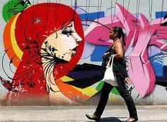 Mulher caminha diante de grafite em rua de São Paulo (Foto: Sandro Fortunato / Reprodução)