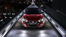 2016 Nissan Maxima sedan shown in Coulis Red from a front angle driving on an illuminated road in the city at night