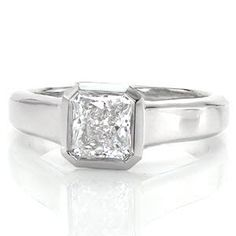 Cashmere is a luxurious design featuring a 1.0 carat radiant cut diamond. The mirrored bezel securely and precisely borders the dramatic octagonal lines of the stone. The wide band tapers to the bottom, giving importance to the brilliant center. Triangular open pockets add dimension and character to the side of the band.