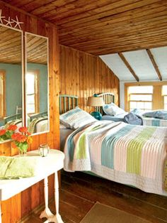 Wood paneling and a vaulted ceiling gives this bedroom a cozy, vintage feel. Simple striped bed linens and blue and green accents are wonderful