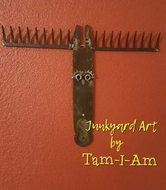 Junkyard Art by Tam-I-Am. Repurposed chainsaw bar and garden rakes make this fun fella. Scrap metal art.