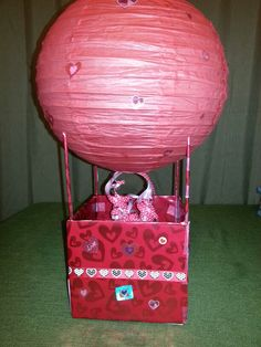 Valentine's Box for school. Hot air balloon. Use wrapping paper to cover a box, the size of a shoe box or Kleenex box. Use skewers to hold up the paper lantern. Use predone curling ribbon. Heart stickers and double sided tape. All items purchased at Hobby Lobby. So many different ways you can make this.
