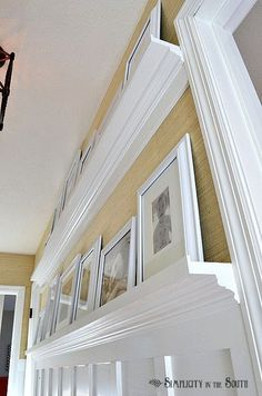 Need ideas for decorating your outdated hallway on a budget? This hallway was given board and batten wainscoting, DIY gallery wall shelves, new carriage style lighting, a DIY decorative air return cover and wallpaper #hallwaydecoratingideas #boardandbatten #gallerywall #galleryshelves