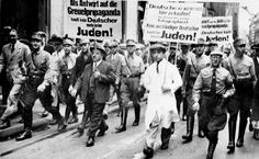 """Koeln, Germany, SA men forcing Jews to march wearing antisemitic signboards, 1933.  The march took place during the economic boycott of the Jews. The signs read: """"In response to the malicious propaganda, Germans! Don't buy from Jews""""."""