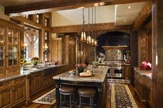 Ultra-rich wood textures fill this ktichen, complete wtih large central dark island, windows up to exposed beam ceiling, and stone-surround hearth in background.