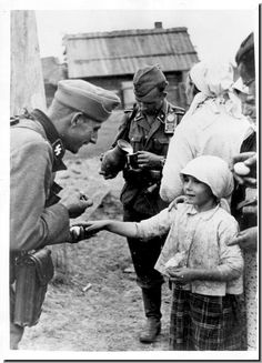 """The """"friendlier"""" face of the Waffen SS. An officer socializes with a Russian girl while villagers ply the Waffen SS with food. A photo with obvious propaganda value. German Soldiers Ww2, German Army, Luftwaffe, Germany Ww2, Man Of War, Ww2 Photos, Mystery Of History, The Third Reich, Military History"""