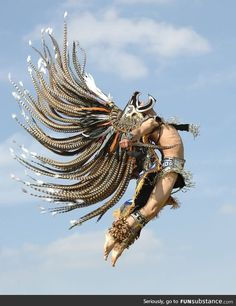 Man in traditional Aztec garb jumping